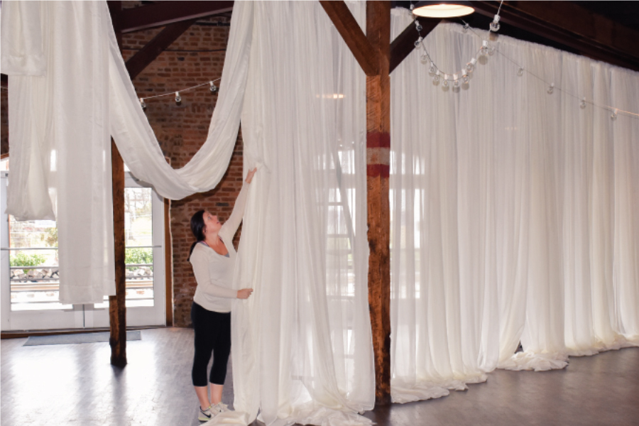 setting up pipe and drape in wedding space sheer white drape